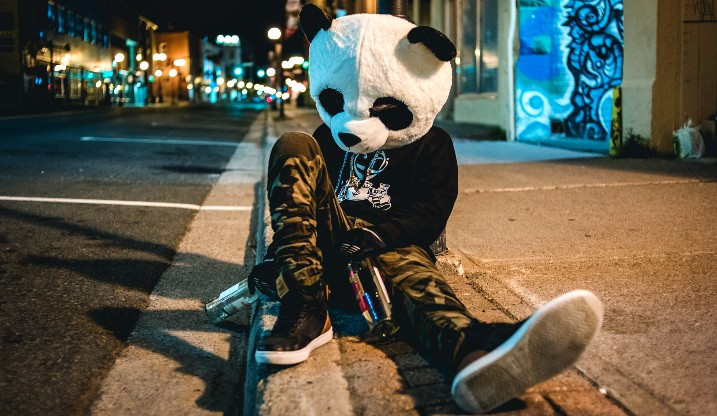 Man sitting on the ground drinking beer and wearing a panda head costume