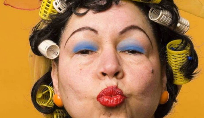 An older woman with strong make up and hair curlers blows a kiss at the camera