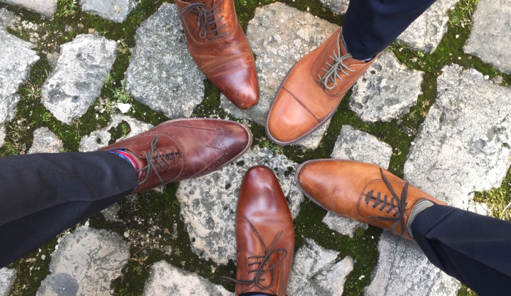 Five men putting one foot forward in a circle wearing dress shoes