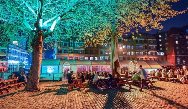 A night time scene of a bar in bristol showing people sitting outside on tables