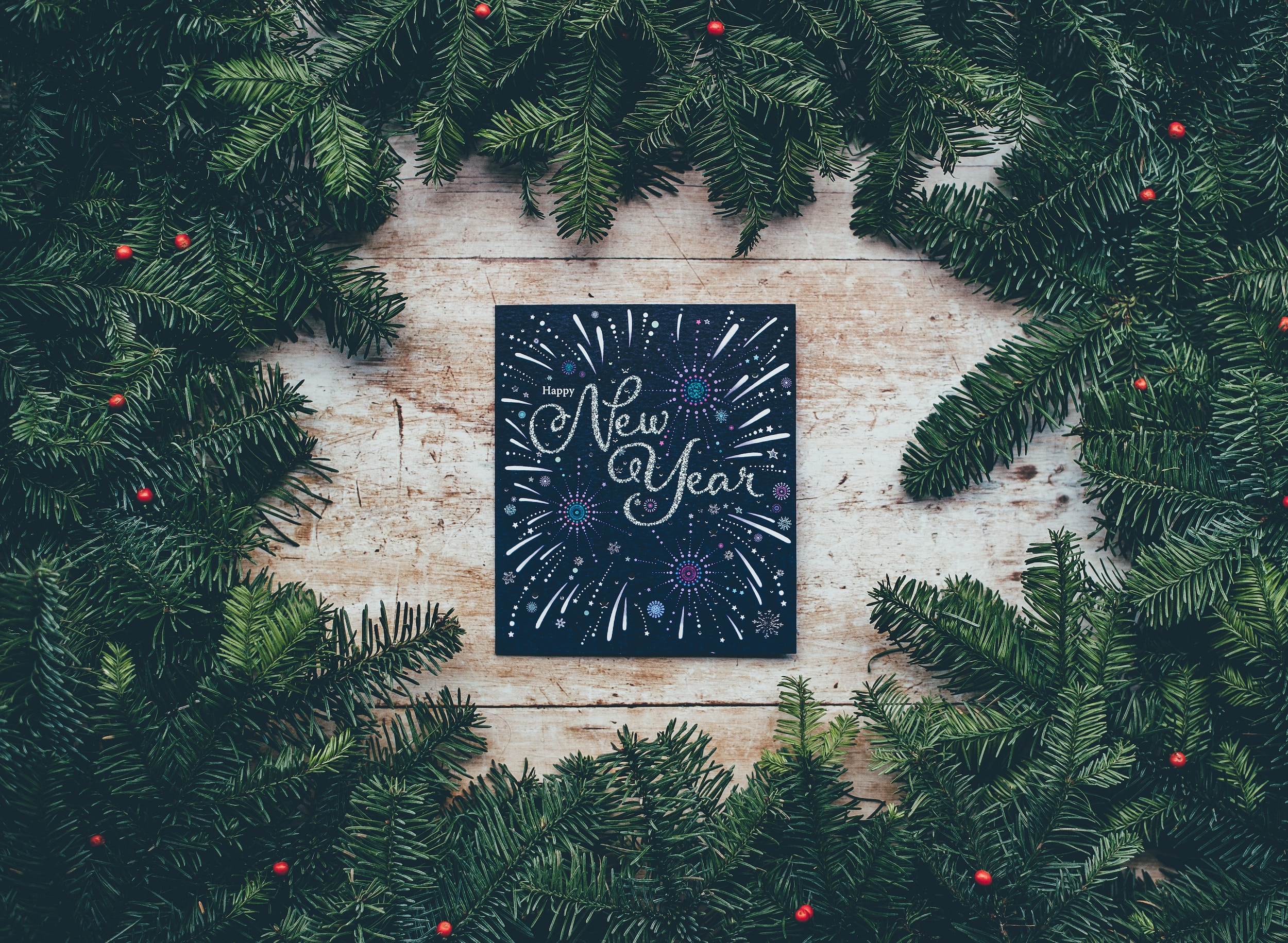 Happy new year sign surrounded by pine tree branches