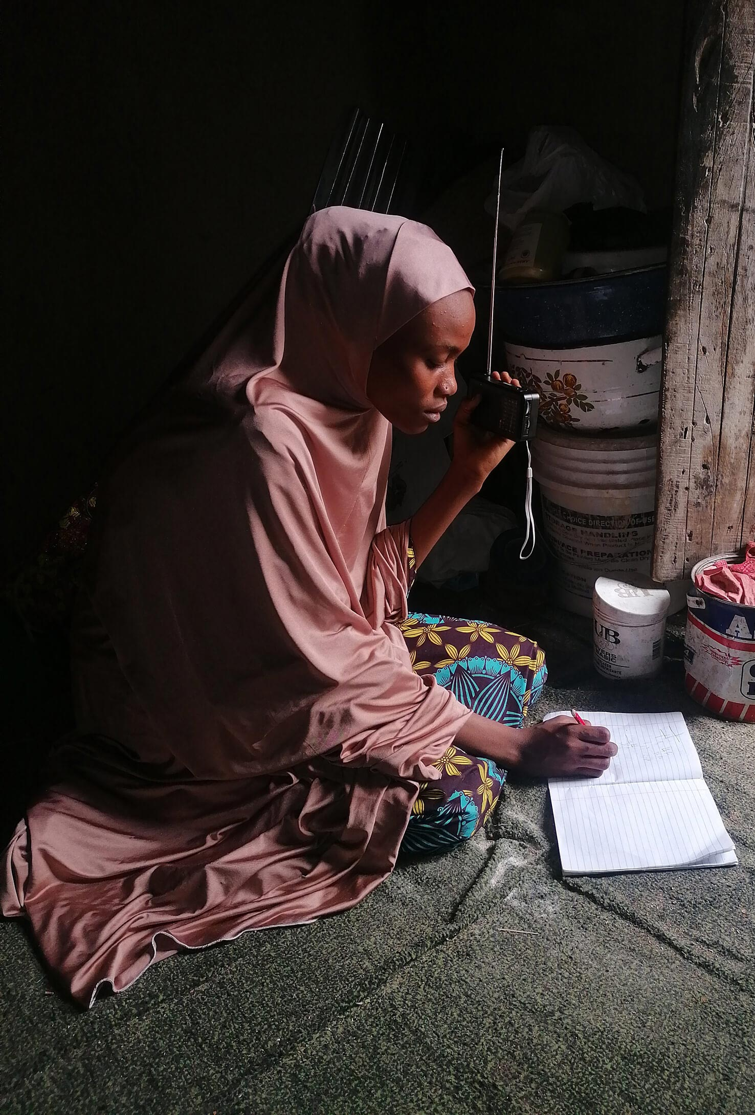 A Nigerian girl listening to radio lessons produced by Malala Fund Education Champions.