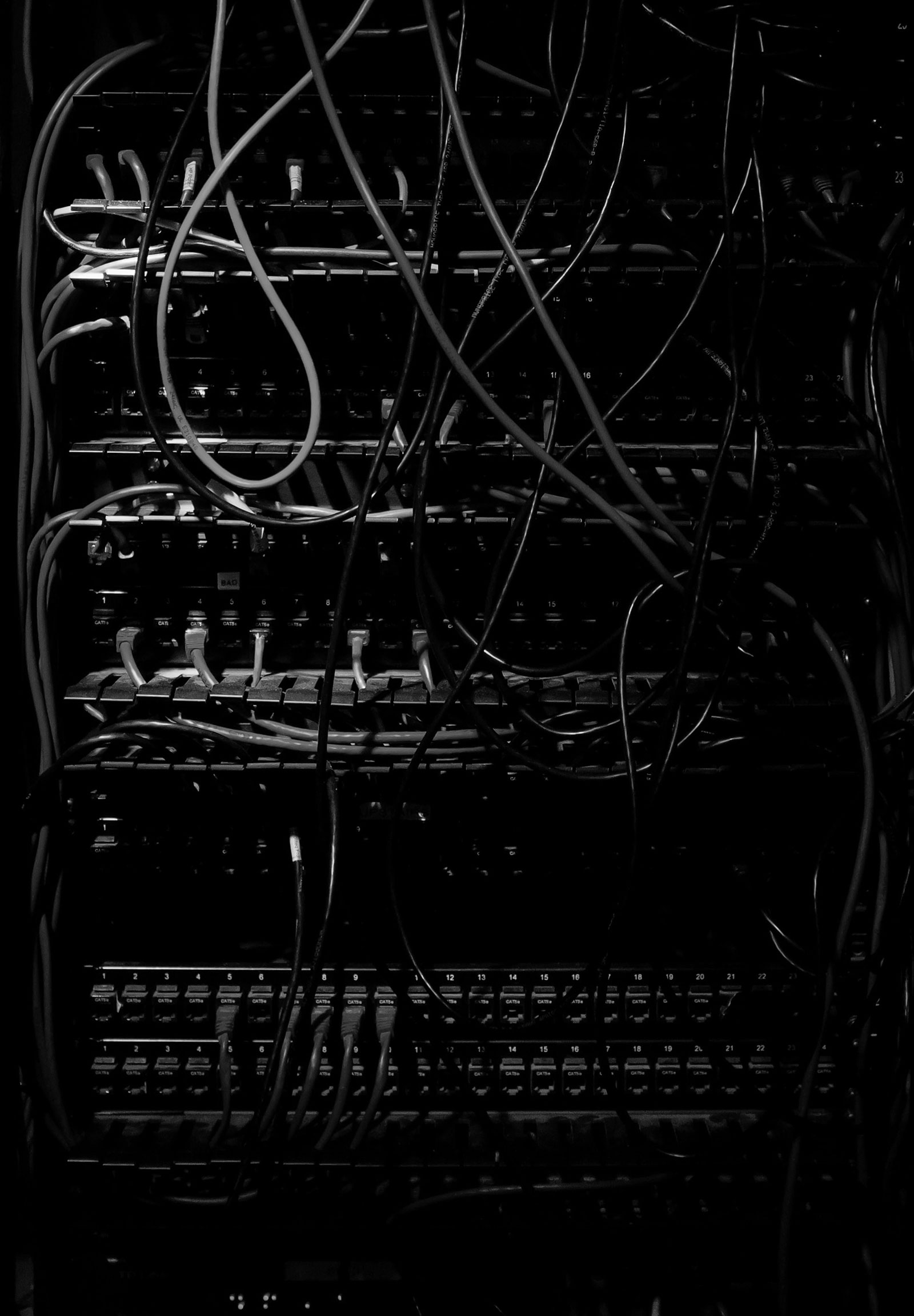 Parts of a dimly lit server rack