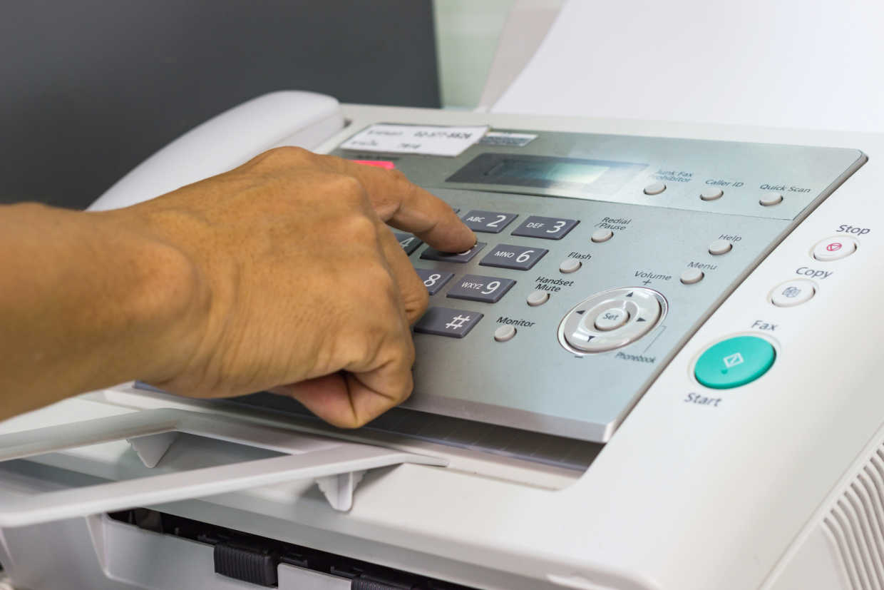 Picture of a hand using a fax machine to send a patient referral
