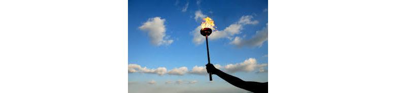 Рука держит факел на фоне неба