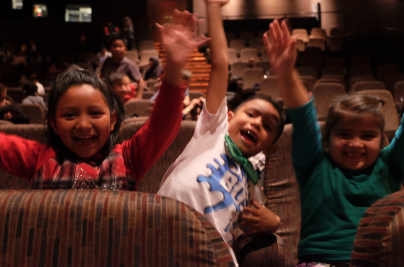 Students pretend they're on a roller coaster in the Paramount Pictures theater.