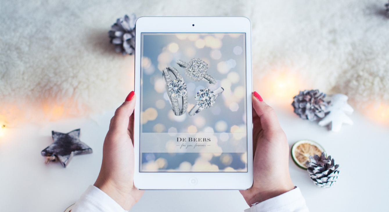 A photo showing hands holding a tablet with De Beers For You Forever app