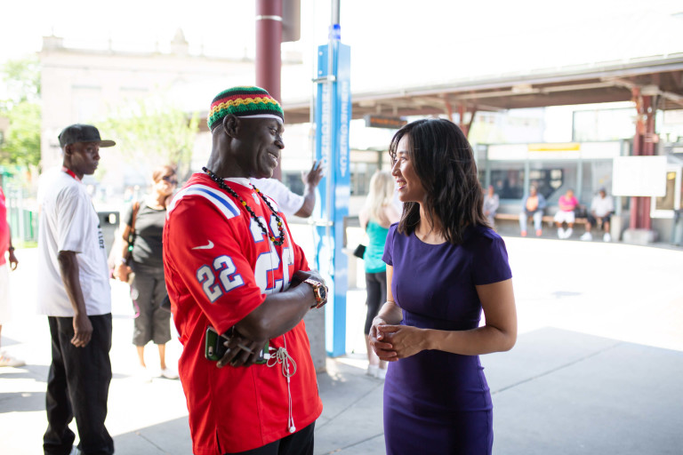 Michelle Wu speaks to a constituent at the Nubian Square bus station.