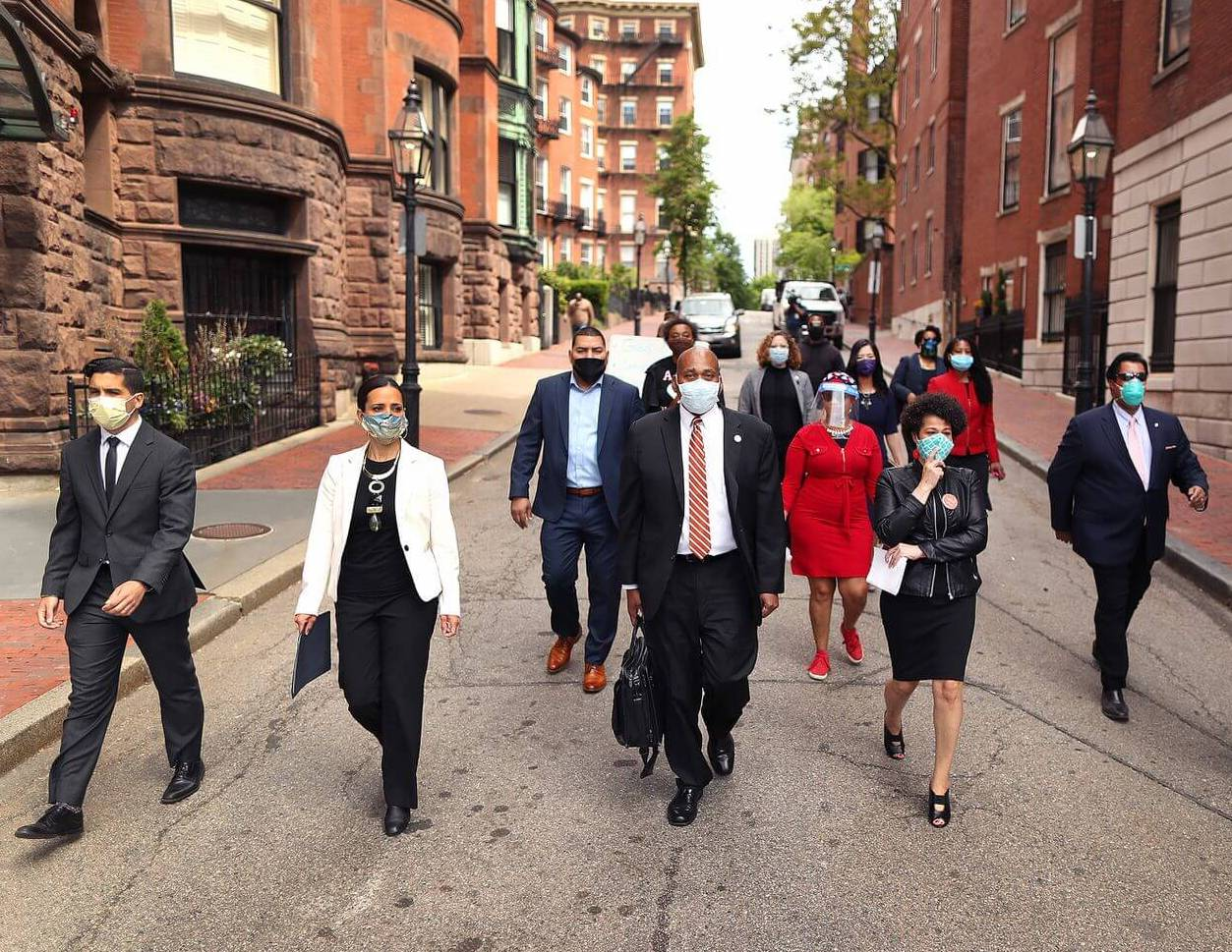 A group of state and local representatives walking in downtown Boston with masks.