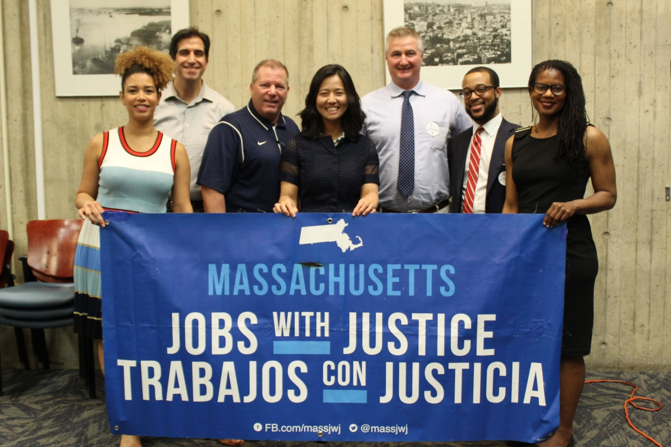Michelle Wu and colleagues hold a Massachusetts Jobs with Justice banner.