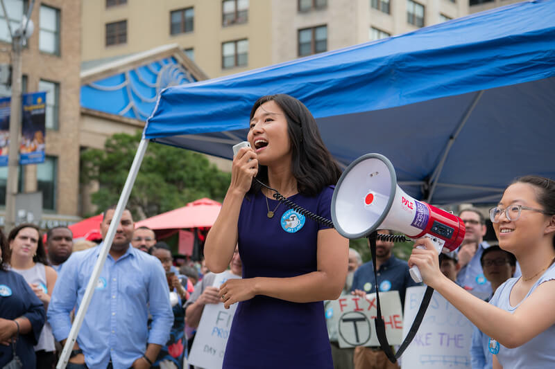 Michelle Wu speaks at  the Free The T rally joined by Brookline Selectman Raul Fernandez, Cambridge City Councilor Jivan Sobrinho-Wheeler, other local elected officials, and commuters.
