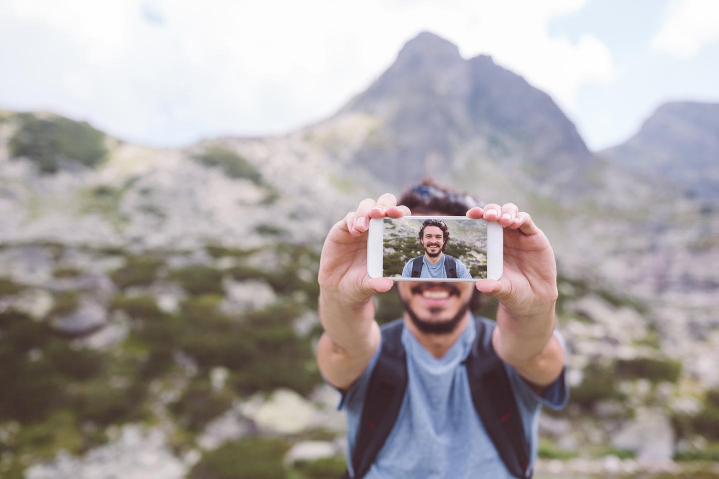 Man on mountain taking selfie