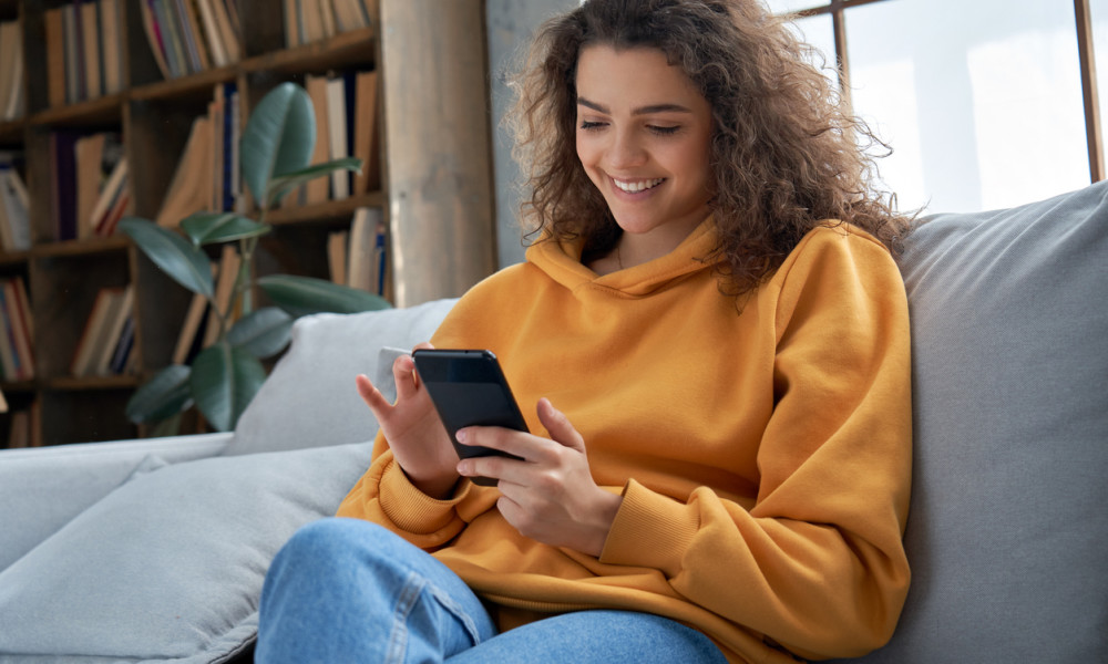 Woman on sitting on couch using her phone