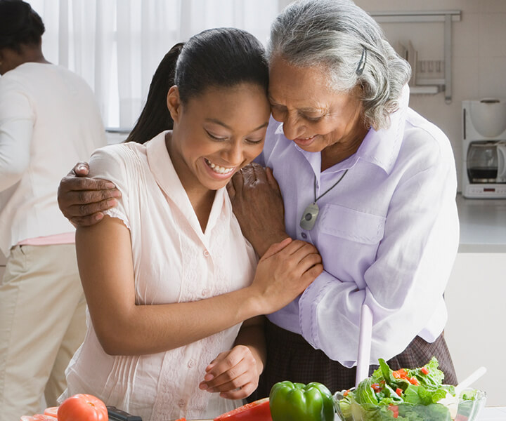 A grandmother and her granddaughter embracing as they prepare food