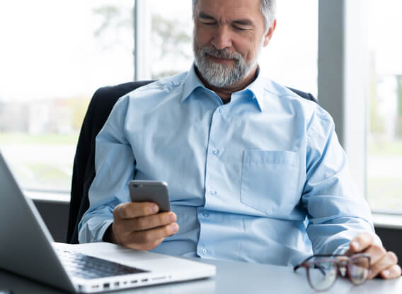 Older man sitting at a desk looking at his phone