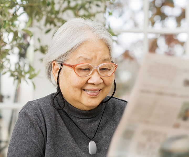 An elderly woman with glasses reading the newspaper.