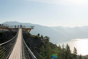 Cable bridge leading to a platform overlooking a lake surrounded by mountains