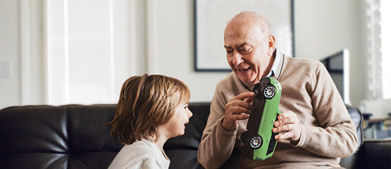 A grandfather playing with his grandchild holding a toy car