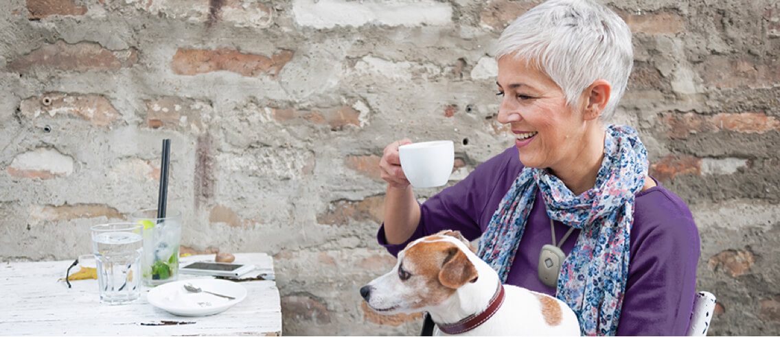 Woman sitting with her dog in her lap enjoying a cup of coffee while wearing the LivingWell Companion Go