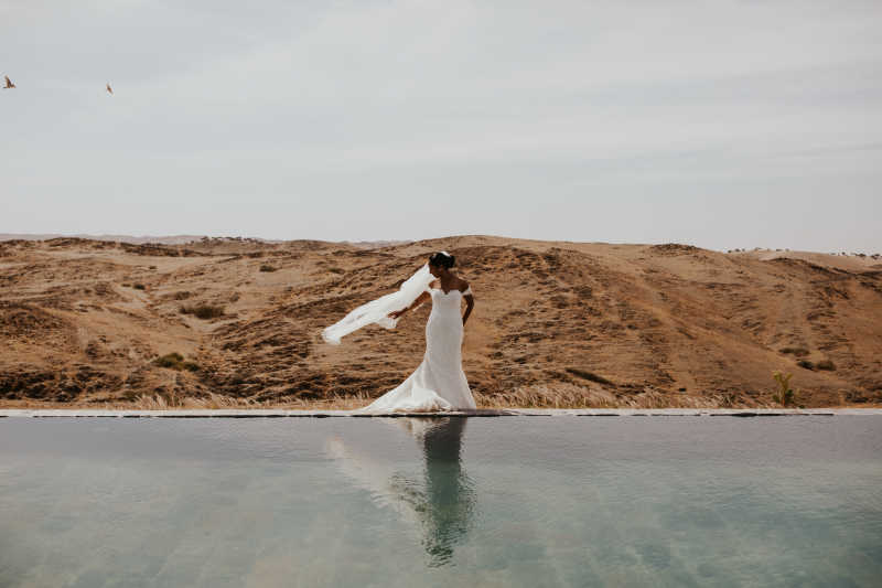 Styled shoot : a bride posing in front of a swimming pool in Marrakech desert