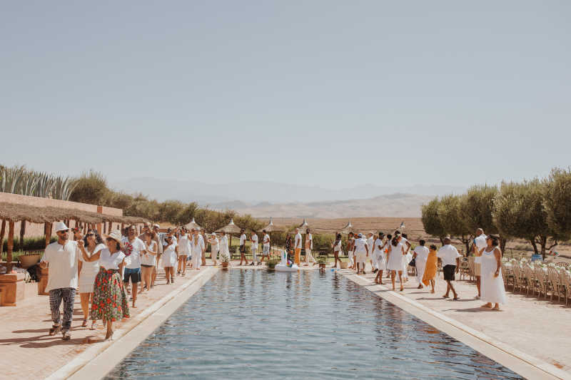 Couple and guests pool partying after wedding celebration in Marrakech
