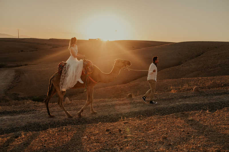 Couple elopement in Moroccan desert, doing a camel ride at sunset