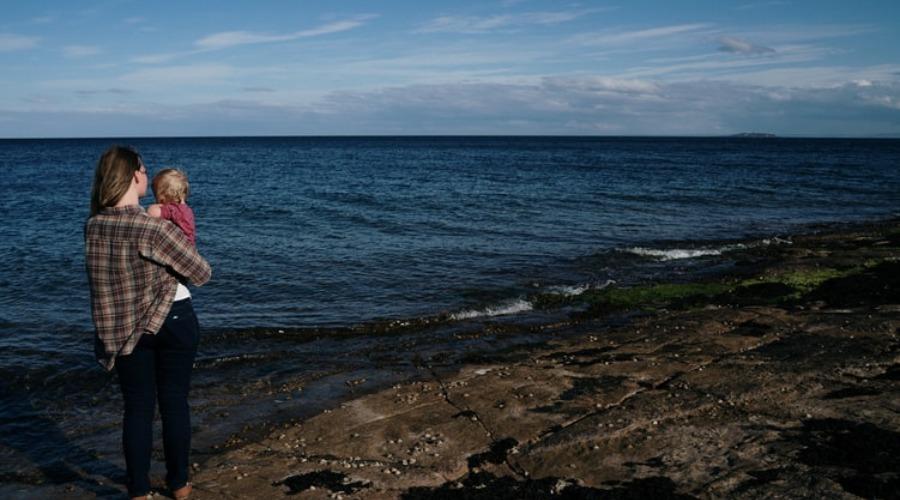 Mama karmiła dziecko na plaży