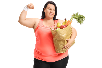 Overweight woman flexing her biceps and holding a bag full of healthy groceries