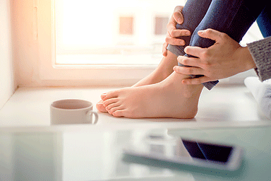 Feet of woman sitting on window sill