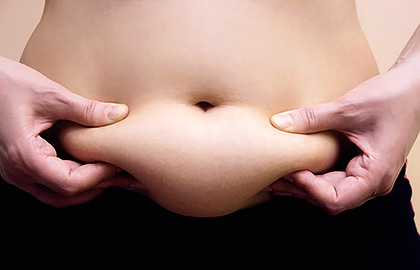 woman squeezing belly fat