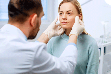 Plastic / Cosmetic Surgeon examines woman's face with gloved hands