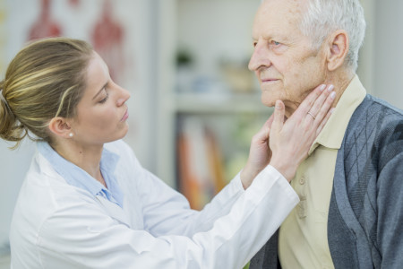 A female dermatologist checking elderly man for skin infections