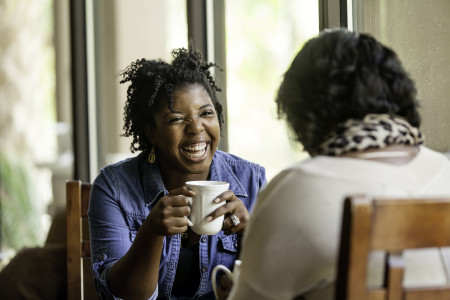 African American women having a good while drinking coffee