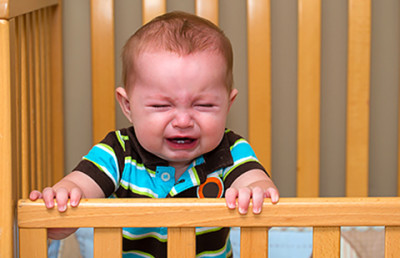 Baby crying in crib. Itchy eczema can cause sleep loss.