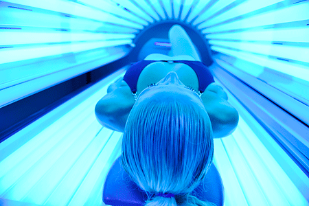 Young woman lying inside a tanning bed
