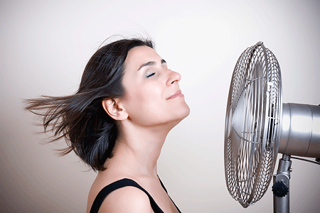 A fan blowing a woman's short brown hair behind her