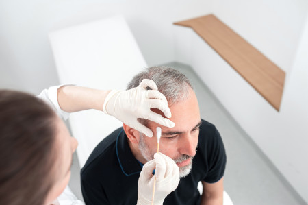 doctor applying medicine to man's forehead