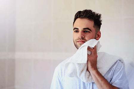 Young man drying his face with a towel in the bathroom