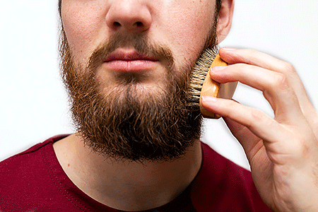 Man gently brushing his beard with a beard brush.