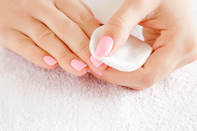 Woman's hand removing pink nail polish with white cotton pad on white towel