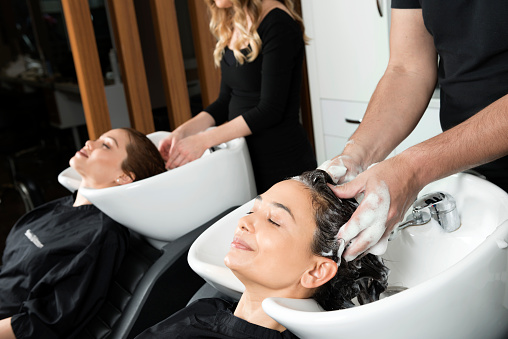 Women getting hair washed at salon