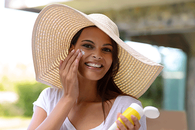 A young woman wearing a wide brimmed hat and applying sunscreen to her face
