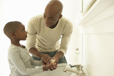 Father and son washing hands with soap in bathroom sink