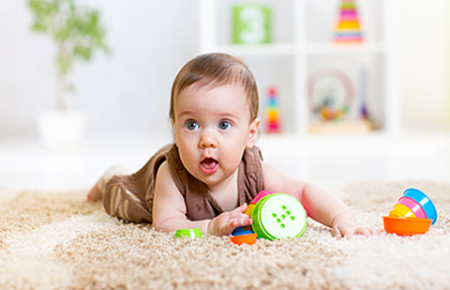 Baby on rug with toys