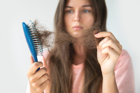 woman pulling hair from brush