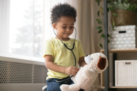 Toddler listening to a stuffed animal's heart with a stethoscope.