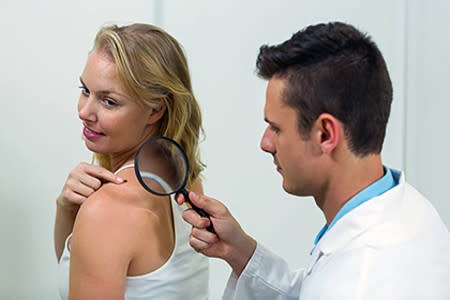 Woman pointing to a mole on her shoulder while getting a skin exam from her dermatologist