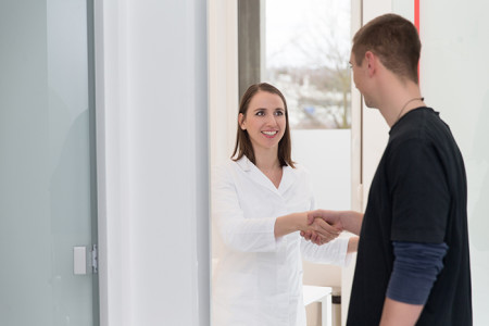 Doctor shaking a young adult patient's hand