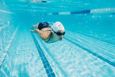 Woman underwater, swimming laps in pool