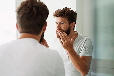 Bearded man checking his skin.